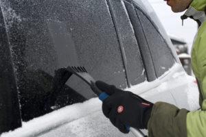 Ein Mann benutzt einen Eiskratzer für sein Auto.