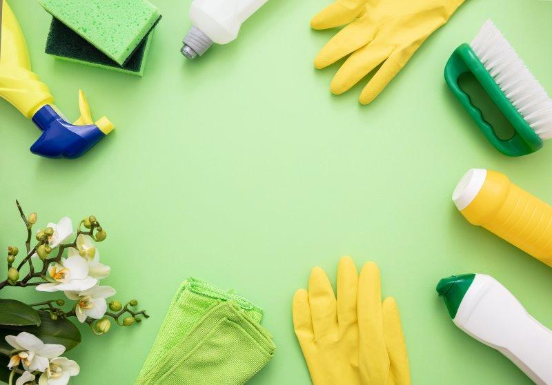 Mehrere Putzutensilien, darunter Essigreiniger, Gummihandschuhe, Reinigungsprodukte und Lappen