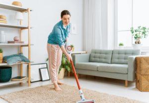eine Frau saugt mit einem kabellosen Staubsauger den Teppich