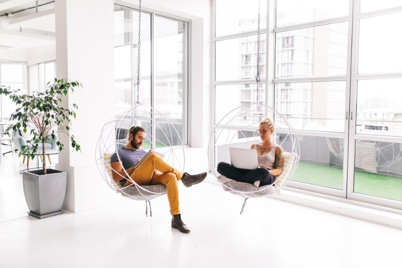 Zwei Menschen sitzen in Korbhängesesseln und arbeiten