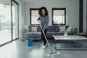 Frau mit Bodenwischer in einer Wohnung