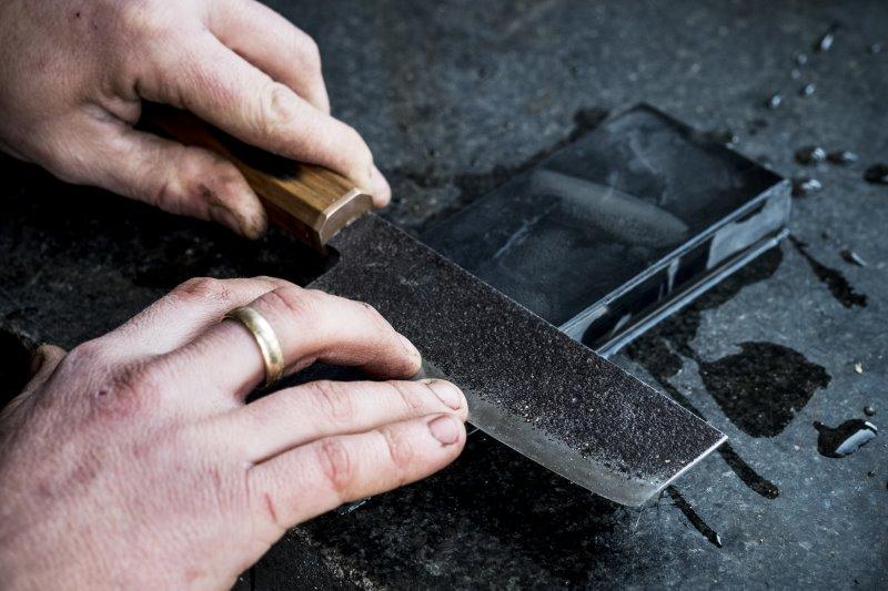 Ein japanisches Messer wird mit einem Schleifstein geschliffen.
