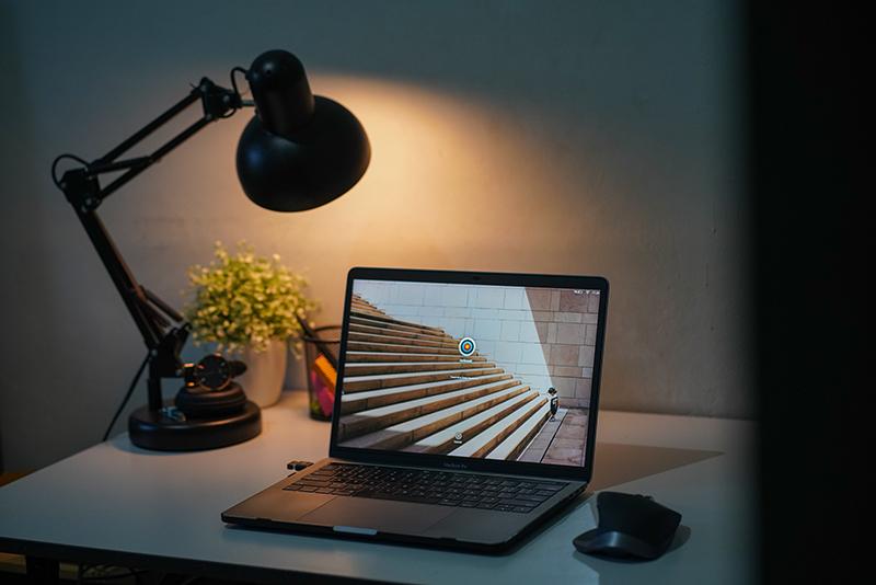 Schreibtischlampe leuchtet im Hintergrund eines Laptops