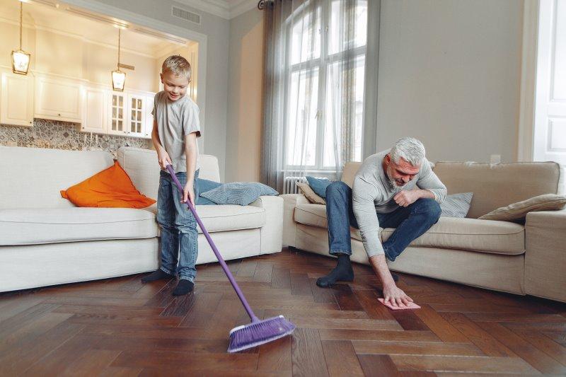 Ein kleiner Junge und ein älterer Mann wischen und fegen den Boden