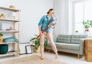 Frau reinigt glücklich ihre Wohnung mit einem Stausauger mit Wischfunktion