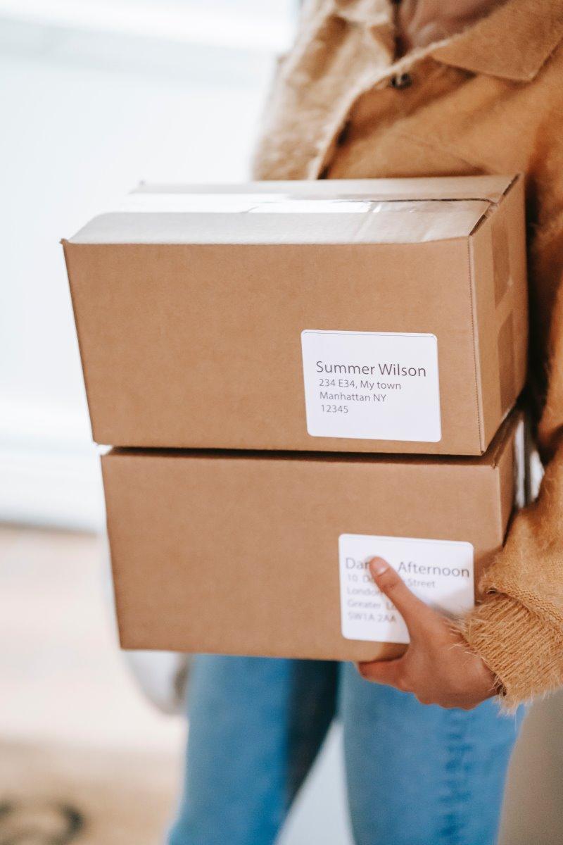 Frau trägt zwei Pakete mit aufgeklebten Versandlabeln