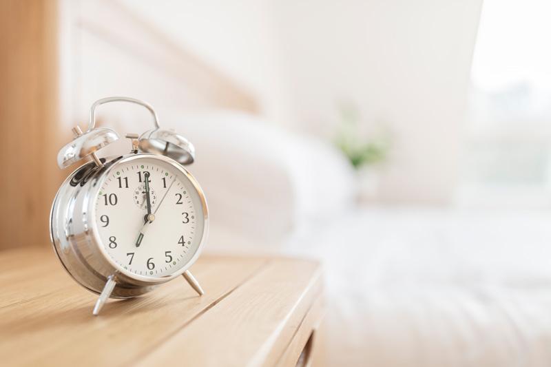 Analoger Wecker im klassischen Design auf einem Nachttisch, im Hintergrund ein Bett