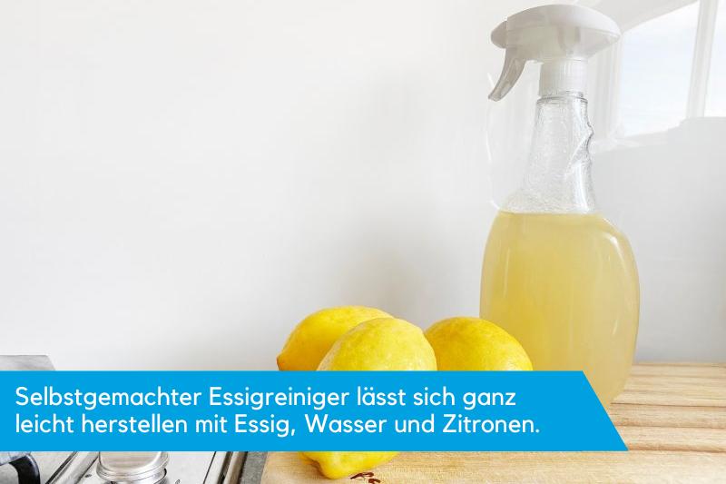 Eine Sprühflasche mit gelber Flüssigkeit und Zitronen davor