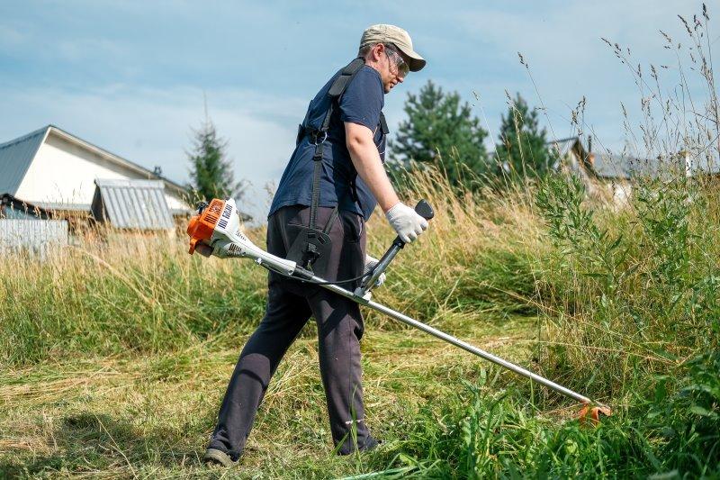 Mann mäht Wiese mit hhem Gras mit einem Freischneider.