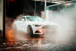 Ein weißes Auto, welches in der Dunkelheit mit Wasser besprüht wird.