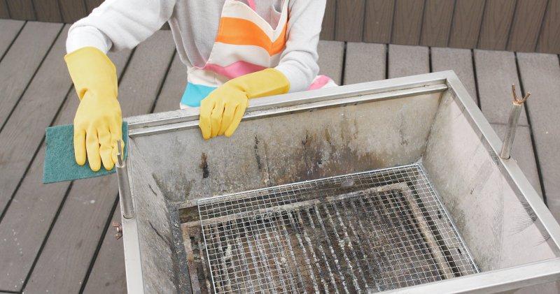 Frau putzt schmutzigen Grill mit Lappen und Handschuhen.