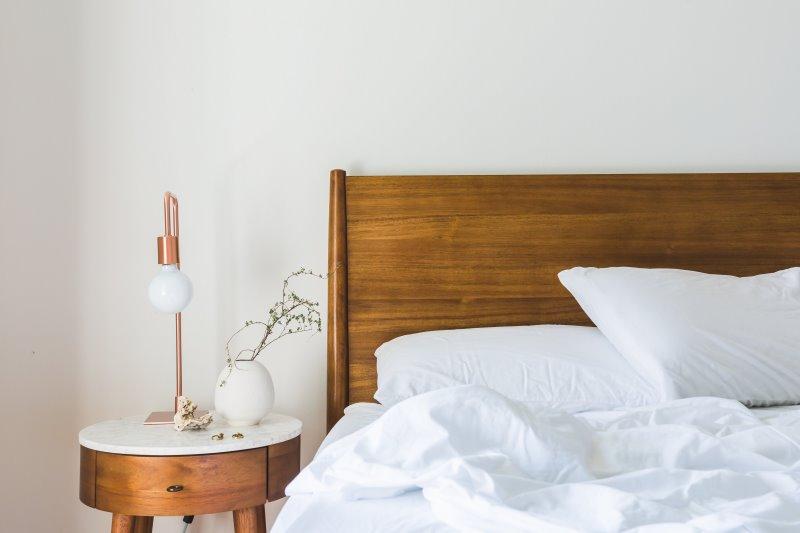 Matratzenauflage und Bettwäsche auf einem Bett und Nachttisch
