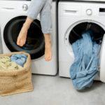Frau sitzt auf einem Kondenstrockner und einer Waschmaschine
