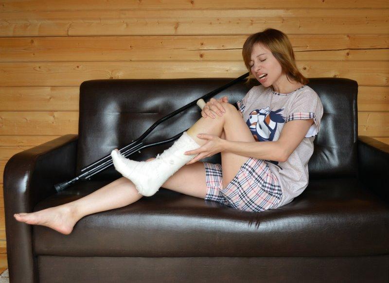 Frau mit gebrochenem, eingegipsten Bein auf einer Couch