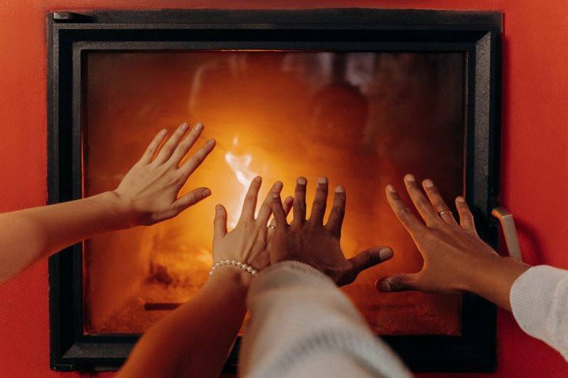 Vier Hände wärmen sich vor dem Pelletofen