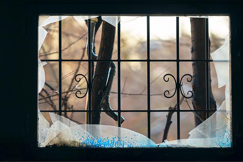 Ein zerbrochenes Fenster mit Gitterstangen