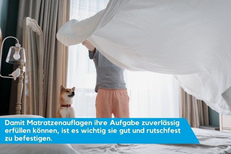 Mann legt Matratzenauflage auf mit seinem Hund