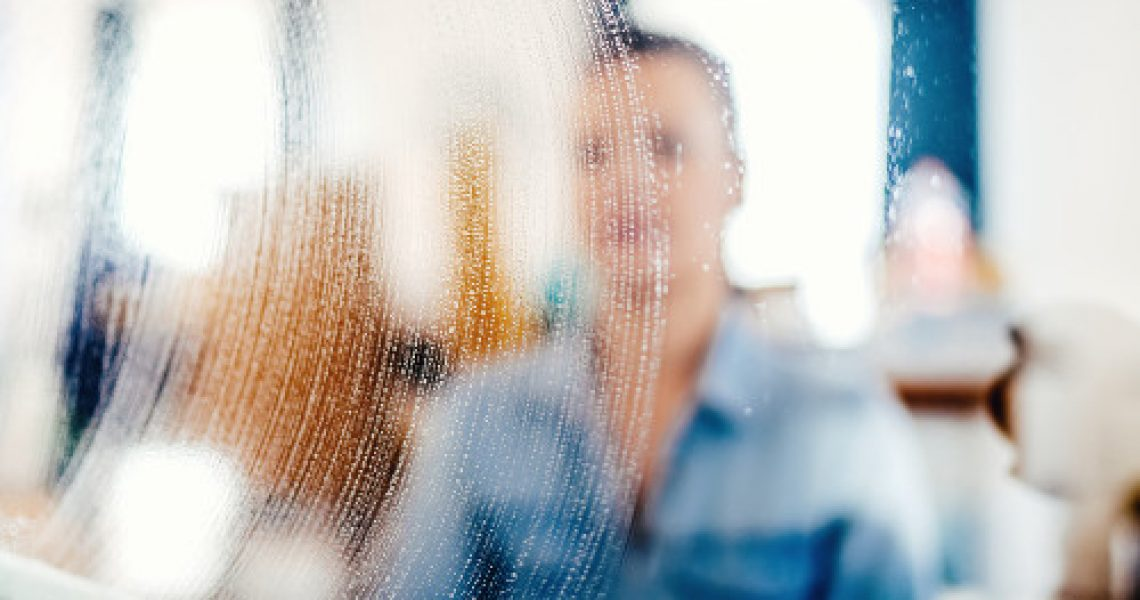 close up portrait, blurred out details of window cleaning. Soap detergent and cloth on window glass
