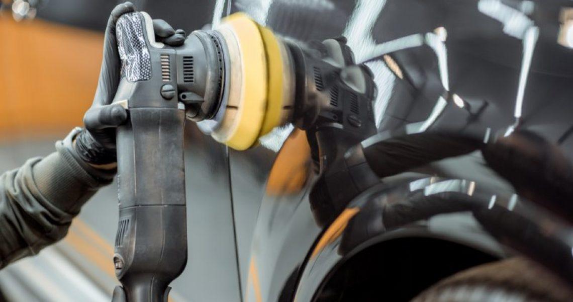 Eine Poliermaschine wird an einem schwarzen Auto zur professionellen Aufbereitung genutzt