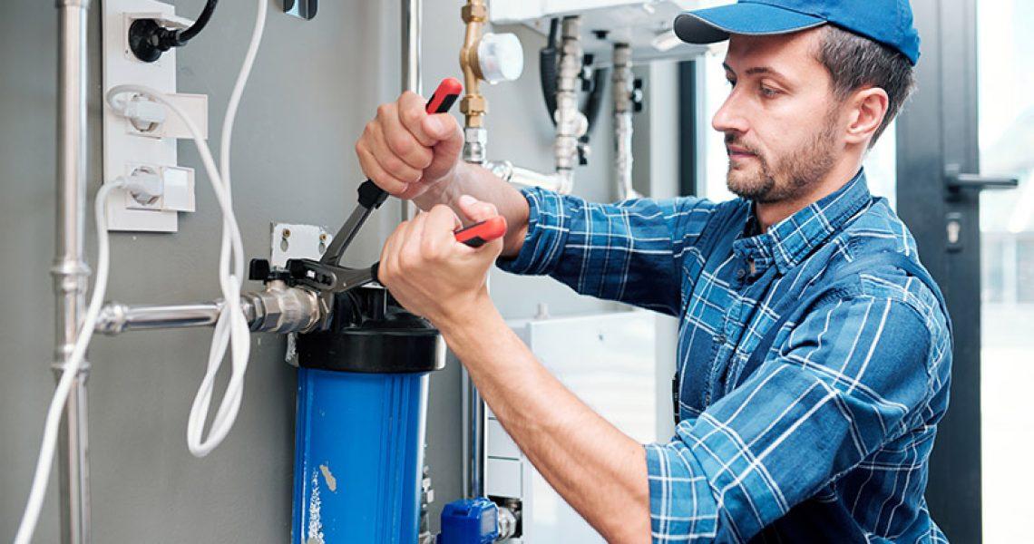 Ein Handwerker installiert einen Hauswasserfilter